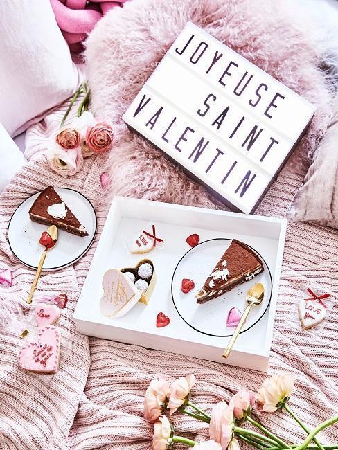 décoratation de saint valentin sur un lit avec un plateau et des gateaux