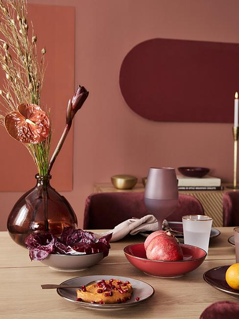 Table en bois avec vaisselle dépareillée et mur corail