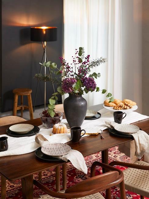 décoration de table avec assiettes noires et beige sur une table en bois foncé