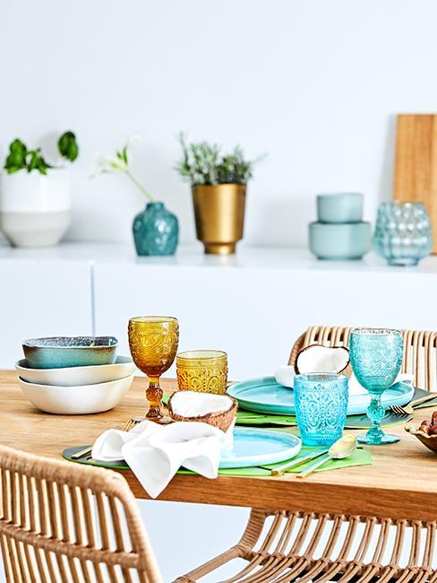 table en bois avec assiettes et verres turquoises