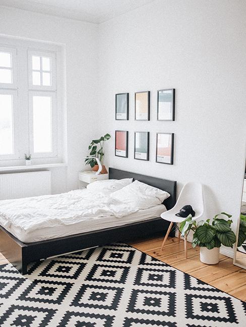Chambre avec murs blancs, tapic graphique, tableaux accrochés au mur