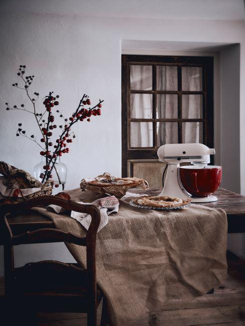 table en bois, nappe en lin beige, kitchenaid blanc et bouquet automnale