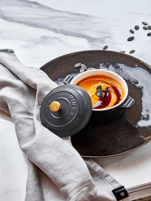 soupe au potiron dans un bol à soupe en céramique noire, serviette grise
