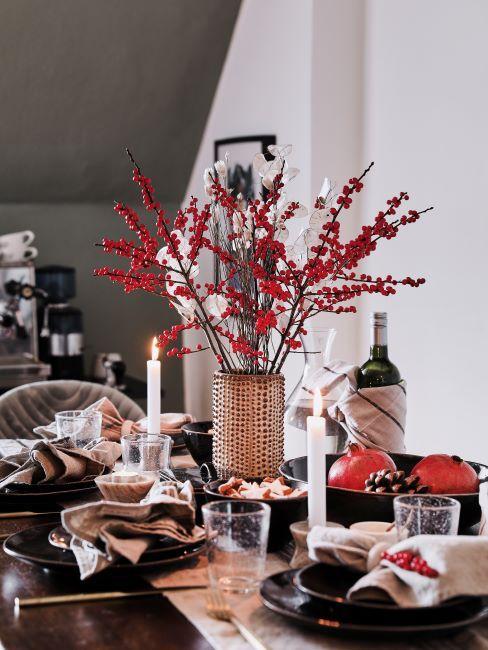 Table décorée en automne, bouquet de fleurs rouges, bougies, vin rouge