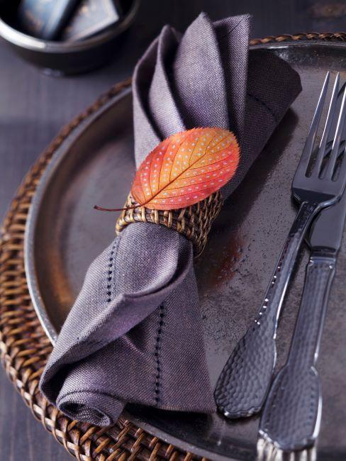 serviette de table mauve, assiette de présentation brune, couverts vintage, feuille d'automne