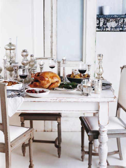 Table blanche, style country, vaiselle blanche, chaises en bois, chandelier et verres de vin