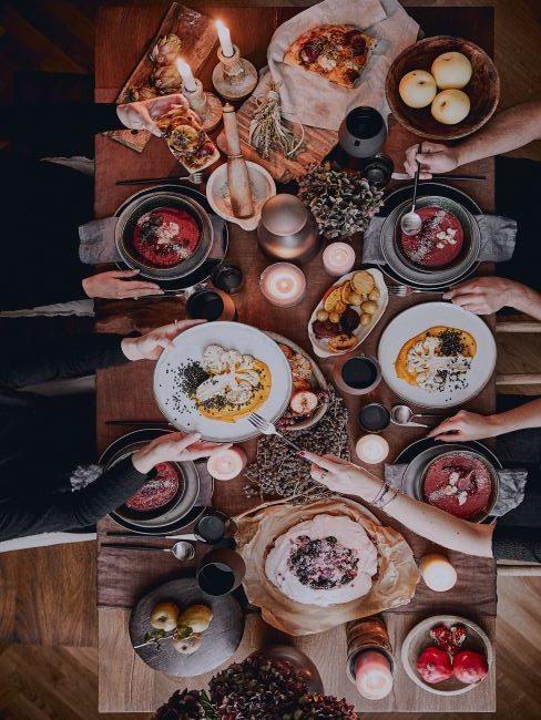 Repas entre amis en automne, divers plats, vaisselle rouge et grise