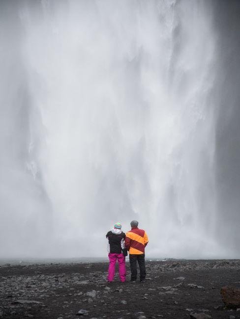 Islande, couple devant une grande chute d'eau