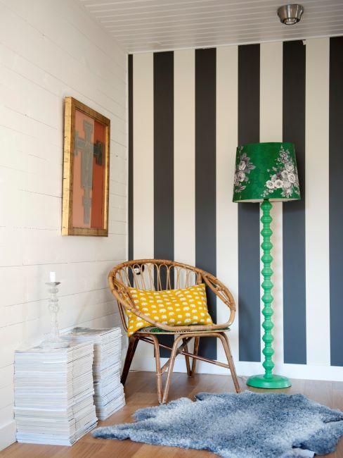 mur rayé verticalement avec fauteuil en rotin et coussin jaune