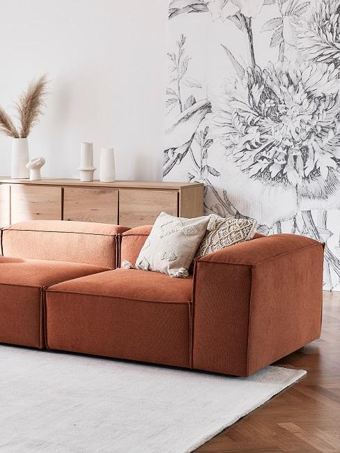 Salon avec papier peint fleurs et canapé terracotta