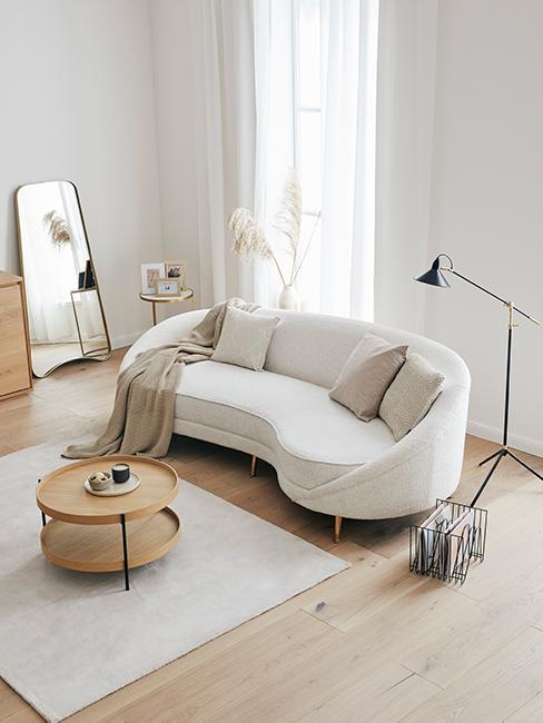 canapé beige demi-lune dans salon blanc