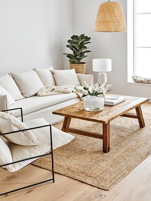 Salon avec tapis en jupe, table basse en bois et canapé blanc