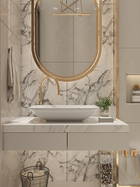 salle de bain avec mur en marbre, miroir dorée et vasque