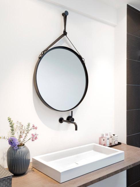vasque blanche avec miroir rond noir en métal et vase