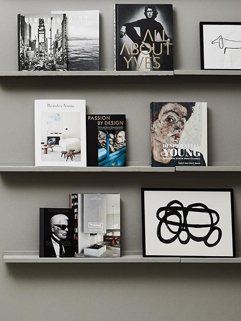 étagère avec livres et cadres accroché sur un mur gris