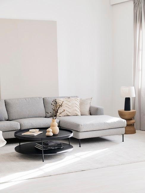 salon minimaliste, murs blanc cassé, table ronde noire, canapé gris