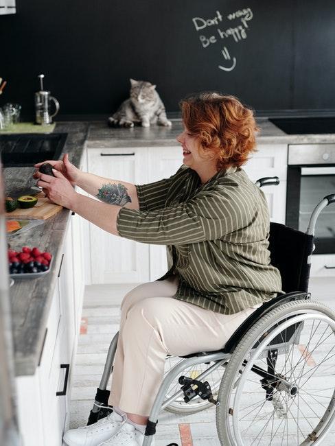 Femme dans sa cuisine, comptoirs blancs et peinture ardoise sur les murs