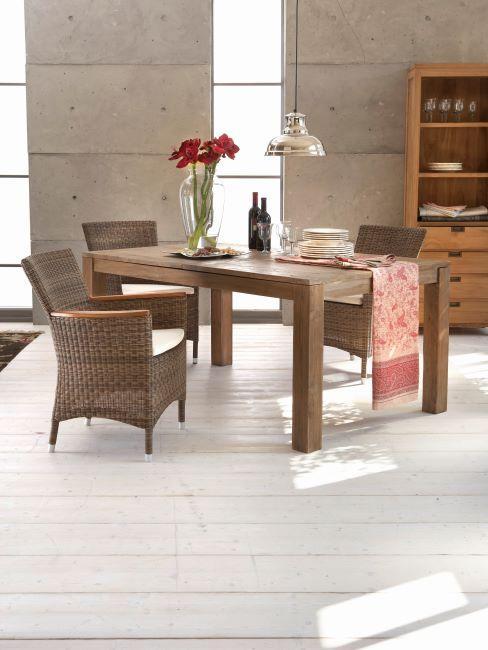 Table en bois massif, fauteuil en rotin et mur en béton style loft