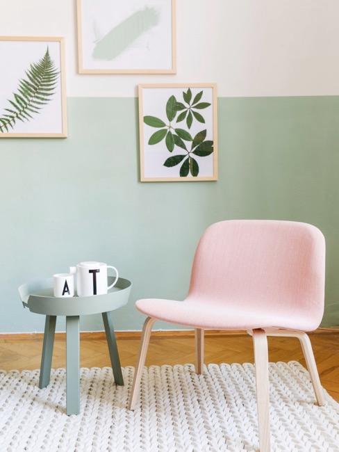 chaise rose pastel, table et mur vert pastel, cadres en bois sur le mur