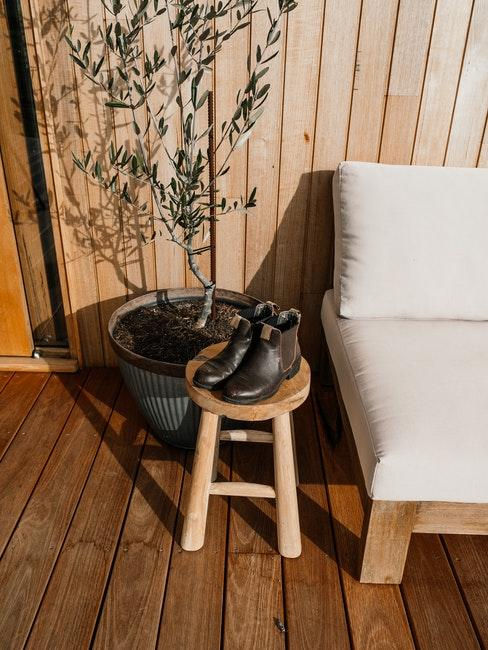 terrasse avec mur et parquet en panneau de bois, tabouret en bois et fauteuil d'extérieur