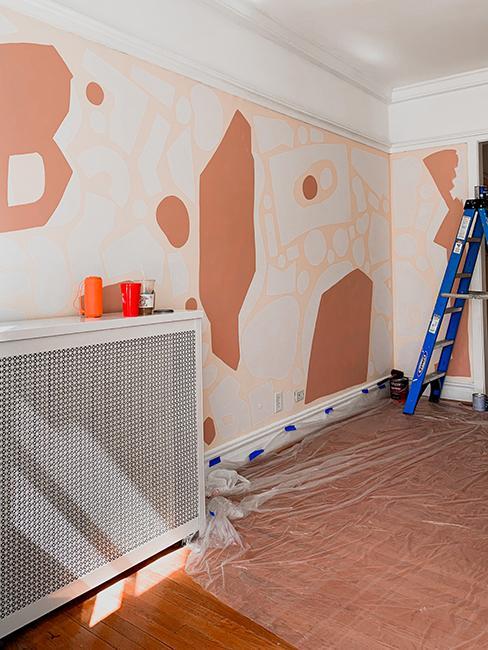Pièce entrain d'être peinte avec des motifs rose et terracotta