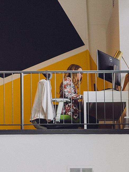 Personne entrain de travailler avec mur géométrique jaune et brun