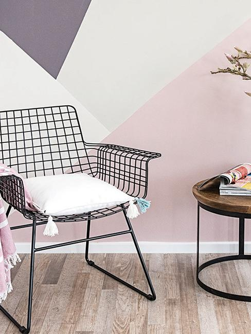 mur avec peinture géométrique et chaise en métal noir