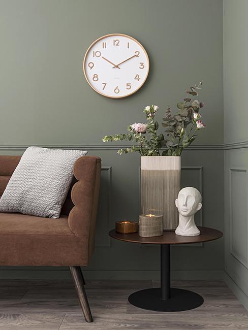 salon avec mur vert olive, canapé brun, horloge murale en bois et table d'appoint