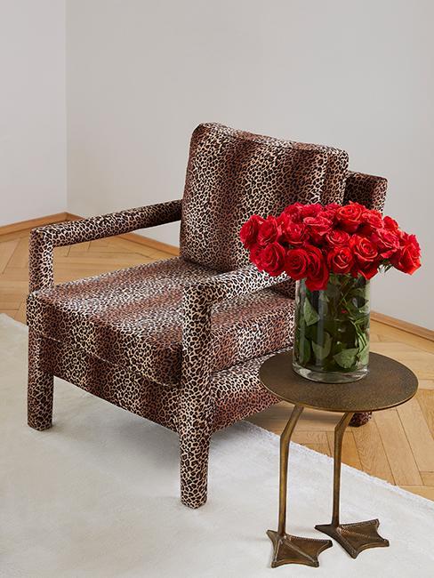 Déco vintage avec un fauteuil à motif animalier, une table d'appoint avec des pattes d'oiseau et un bouquet de fleurs rouges