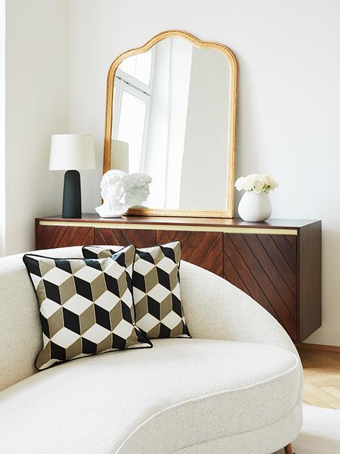 salon style vintage chic avec canapé blanc, coussins à motif, buffet en vois et miroir baroque