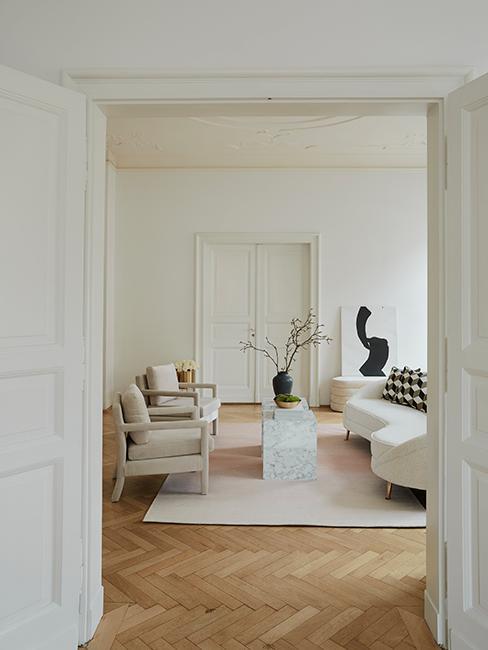 salon avec déco vintage, canapé courbé, fauteuil beige et tapis beige