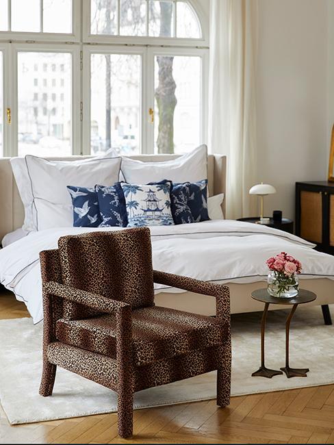 chambre style vintage chic avec fauteuil avec motif animalier, coussins style oriental et linge de lit blanc