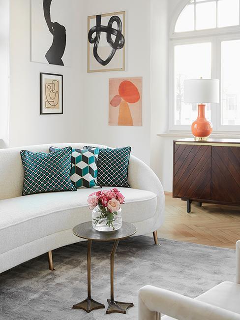 salon style vintage chic avec canapé blanc courbé, coussins bleu vert, cadres affichés au mur et buffet en bois