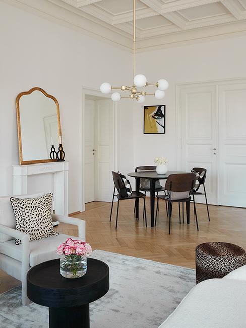 salle à manger avec table ronde et chaises en bois, miroir baroque doré et fauteuil beige
