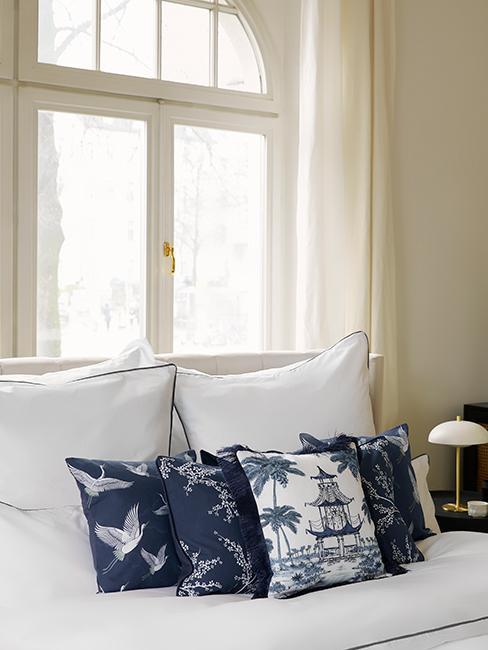 chambre avec linge de lit blanc et coussins décoratifs bleus orientaux