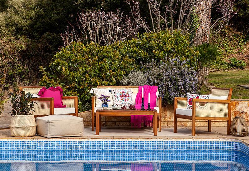 terrasse avec salon de jardin en bois et coussins roses au bord d'une piscine