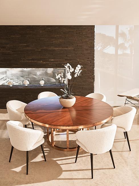 salle à manger avec table ronde en bois et chaises en velours blanches chez Delia Lachance