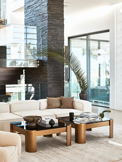 salon avec grand canapé, tables basses rectangulaires et baie vitrée beige chez Delia Lachance