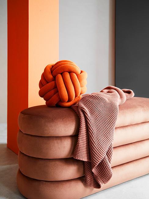 coussin orange en forme de tricol posé sur un banc en velours terracotta