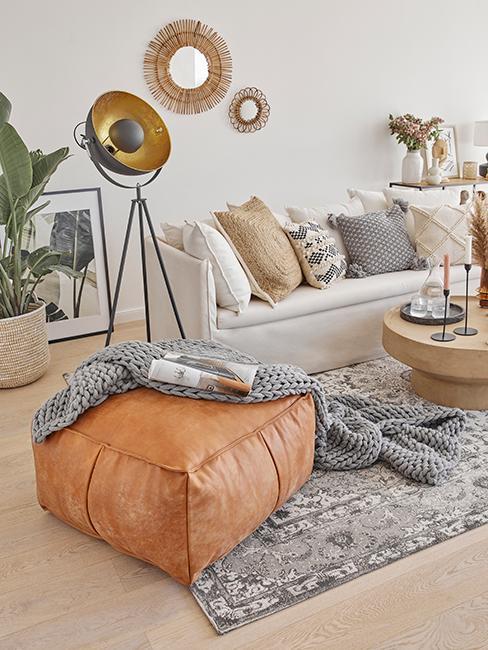 salon bohème avec canapé blanc, pouf brun en cuir posé sur un tapis vintage gris