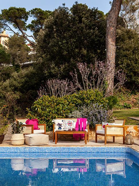 terrasse au bord d'une piscine avec salon de jardin en bois et coussins roses
