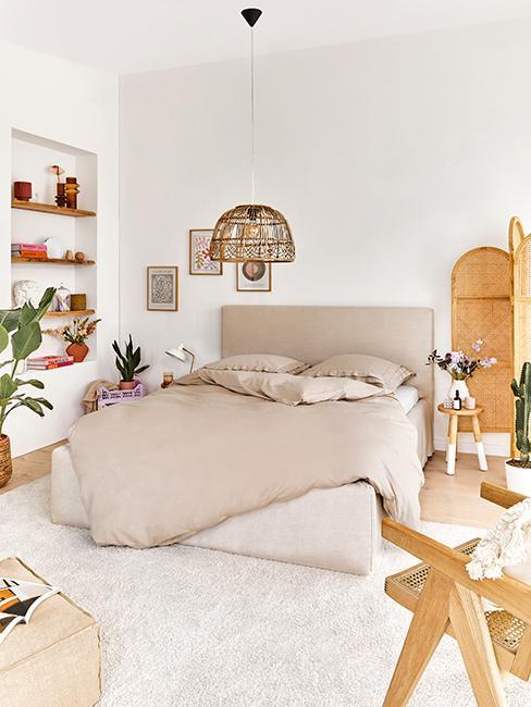 chambre avec grand lit avec couette beige et déco boho
