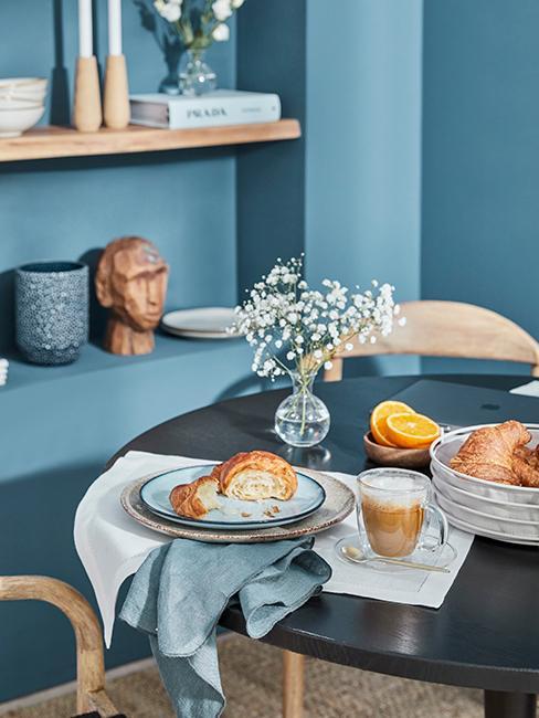 petit déjeuner avec croissant sur une table ronde dans une salle à manger avec les murs bleus