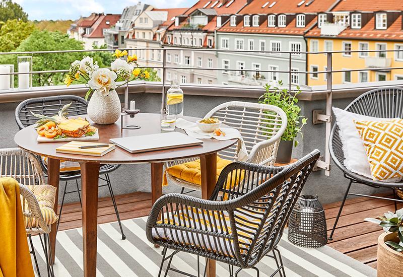 balcon avec chaises grises et plaid jaune