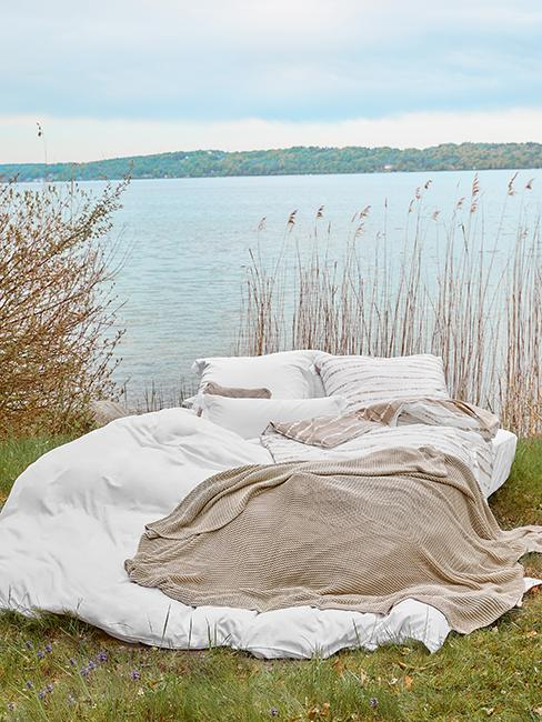 lit posé sur l'herbe près d'un lac