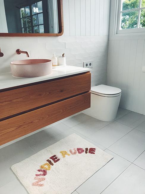 toilette avec tapis de sol et meuble en bois
