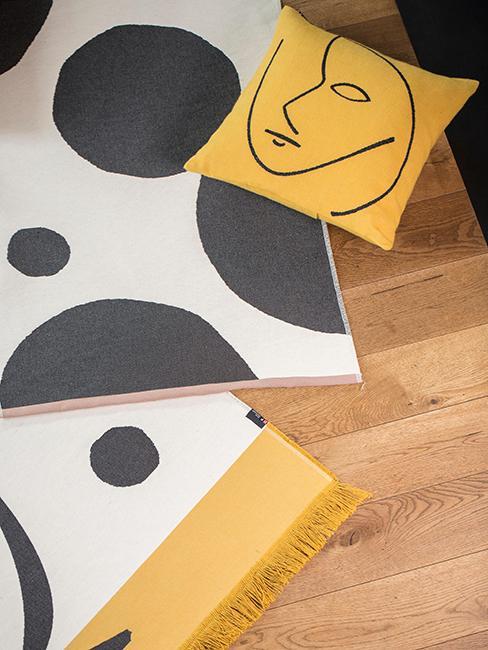 coussin jaune avec motif visage posé au sol sur des tapis