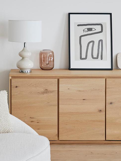 cadre avec affiche visage posé sur un meuble tendance en bois