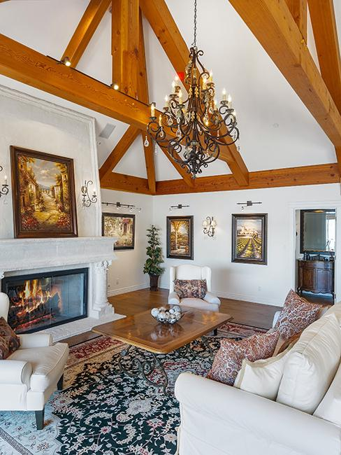 salon chic avec canapé beige, cheminée, poutre apparente et lustre