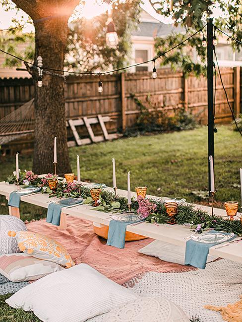 table extérieur dressée avec nappe, décoration de table et bougie dans le jardin